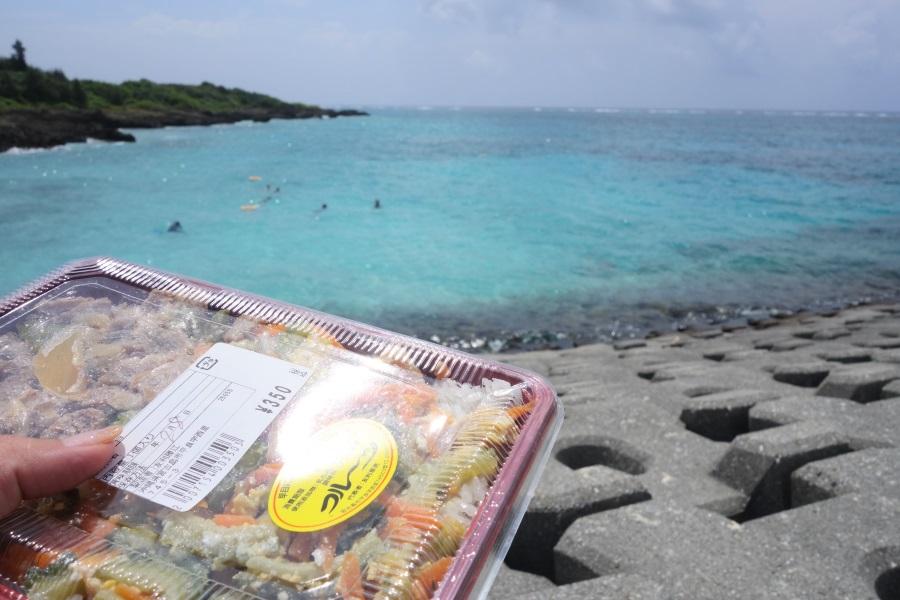 あたらす市場のお弁当を海で食べるところ